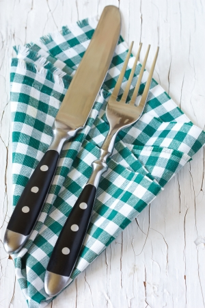 Rustic cutlery with green provence napkin on an old wooden table. photo