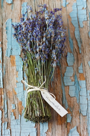 Bunch of lavender flowers with tag on an old blue board.