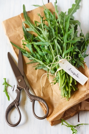 Bunch of fresh arugula with tag and old scissors.