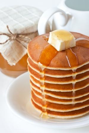 Fresh pancakes with butter and honey on a plate. photo