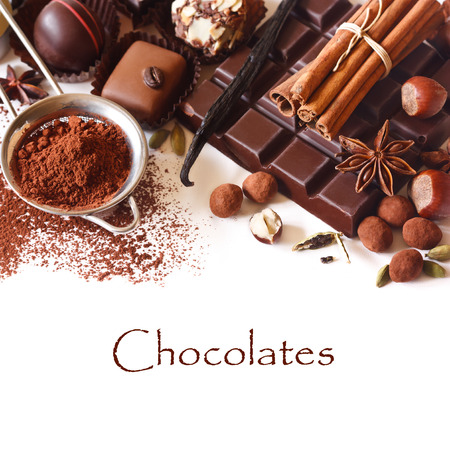 Delicious chocolates and spices on a white background.