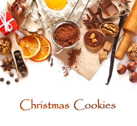 Baking background with cookie ingredients, spices and cookie cutters on a white.