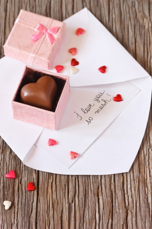 Valentines love letter with chocolate heart on a wooden background. photo
