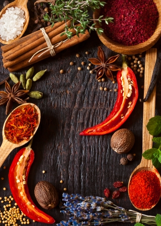 Colorful spices and herbs frame on a wooden background