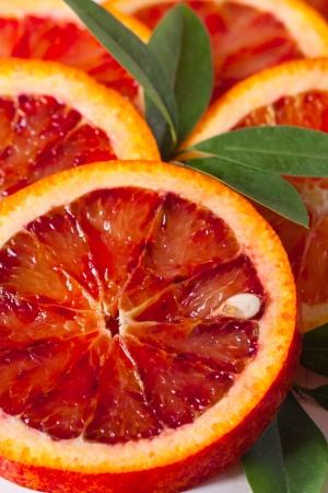 Sliced Sicilian blood red orange with leaf close up. Stock Photo