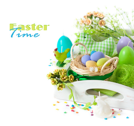 Easter decorations with colorful eggs and funny candles on a white background. photo