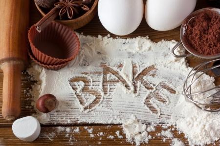 Baking utensils, spices and food ingredients on wooden board close-up. Reklamní fotografie