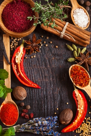 Colorful spices and herbs frame on a wooden background. photo