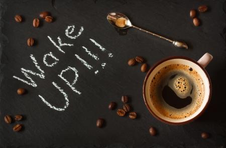 コーヒーのカップと黒い黒板でコーヒー豆。 写真素材