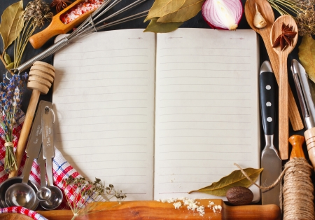 Open recipe book surrounded of food ingredients and kitchen utensils.
