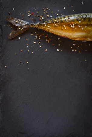 plato de pescado: Pescado ahumado con especias sobre un fondo negro.