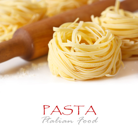 Pasta tagliatelle and wooden rolling pin close-up. photo