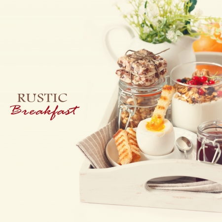 Rustic breakfast with boiled egg and homemade granola on a wooden tray. Toned photo. photo