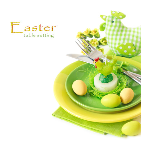 chicken or egg: Easter table setting with chickeh candle and colorful eggs.