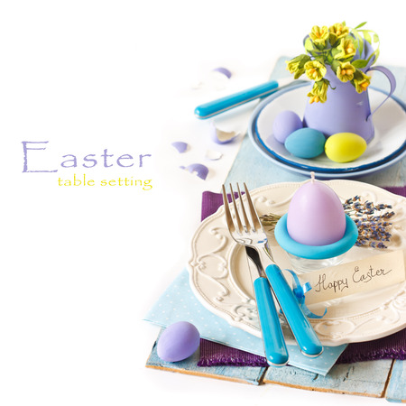 party background: Easter table setting with egg candle and flowers. Stock Photo
