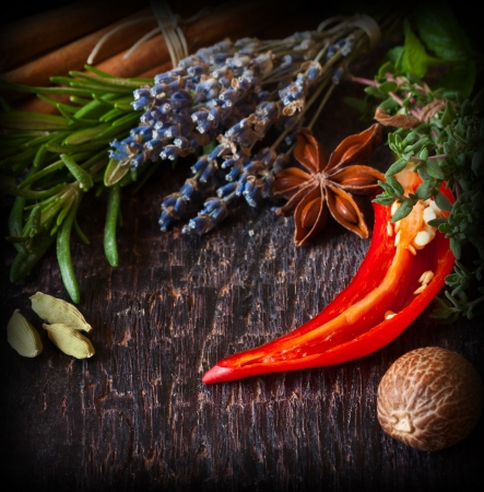 Beautiful spices and herbs on an old dark wooden board photo