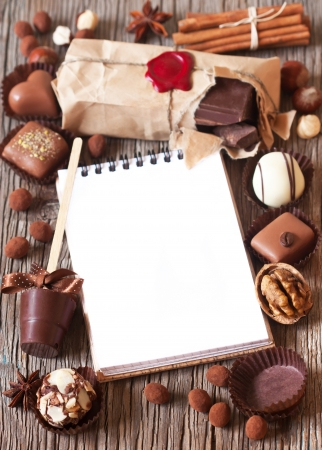 Chocolate and spices frame with notebook for text on a wooden bacrground. photo