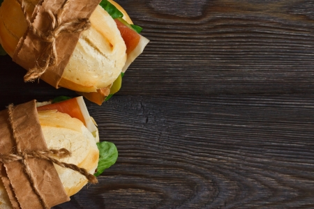 Sandwiches on a wooden background with copy space for text.