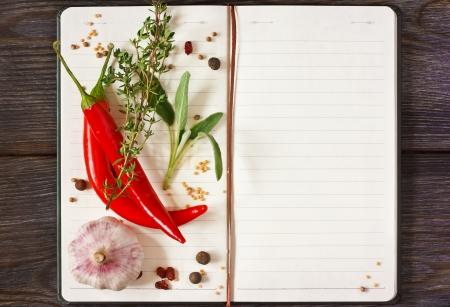 Met chili en kruiden Open receptenboek op een houten achtergrond.