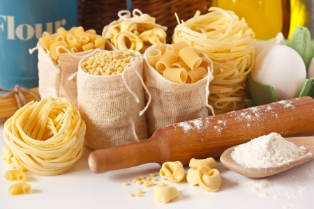 Assortment of pasta and wooden rolling pin close-up.