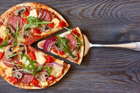 Pizza with salami and arugula on a wooden board.