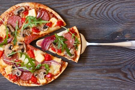 Pizza mit Salami und Rucola auf einem Holzbrett.