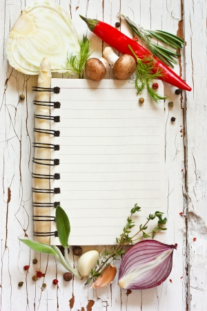 cookbook: Open recipe book with vegetables and herbs on a wooden background.