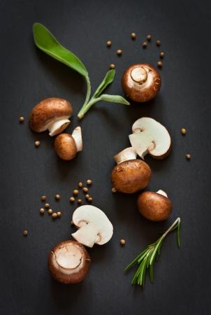 Verse champignons met kruiden en specerijen op een zwarte bord.
