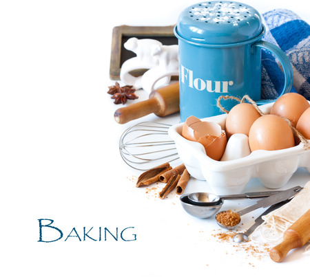 Flour strainer, wooden rolling pin, whisk, measuring spoons and food ingredients for baking on a white. photo