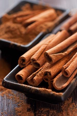 Aromatic cinnamon sticks on a black bowl. Stockfoto