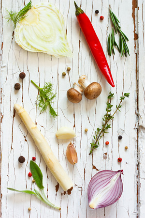 Fresh vegetables and herbs on an old wooden board. photo