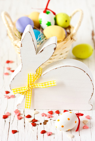 Easter decorations with white wooden bunny and colorful eggs. photo