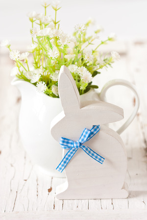 Easter decorations with white wooden bunny and spring flowers. photo