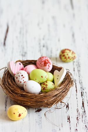 huevos de codorniz: Pascua huevos de chocolate en un pequeño nido en una tabla de madera de color blanco, con copia espacio para el texto.