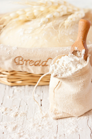 Bag of flour with wooden scoop and fresh homemade dough for bread in a basket on an old white kitchen board. photo