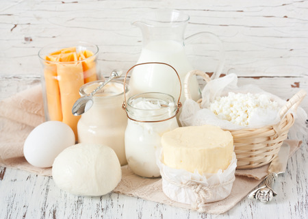 Fresh farm dairy products on a white wooden background. Tasty cheese, butter, eggs, milk and yogurt close-up.