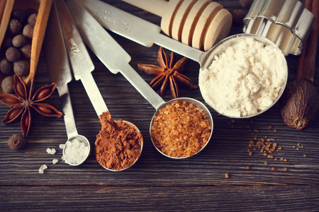 Food ingredients and kitchen utensils for cooking on a wooden board. Measuring spoons with cocoa, flour and brown sugar and spices. Toned photo.