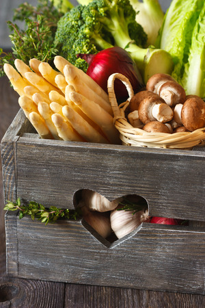 reg: Fresh kitchen garden bunch of white asparagus, reg onion, broccoli, romaine lettuce and garlic bulbs in an old wooden rustic box.