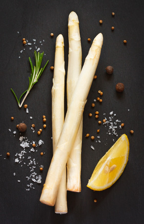 White asparagus and spices on a black