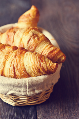 continental breakfast: Fresh croissants for breakfast in a basket on a wooden background. Toned photo.