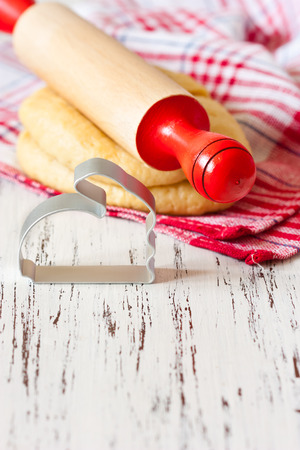 Cooking Easter biscuits. Fresh sweet dough, wooden rolling pin and funny bunny cookie cutter on a white wooden board with place for text. photo