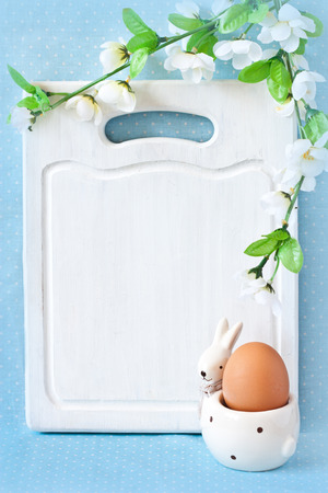 Old white kitchen cutting board with copy-space for writing Easter menu, funny rabbit egg cup and blossom apple tree. photo