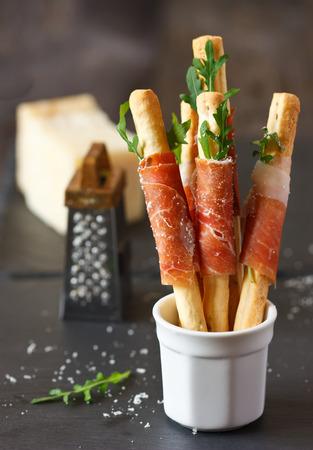 grissini: Grissini bread sticks with prosciutto ham, arugula and parmesan cheese. Stock Photo