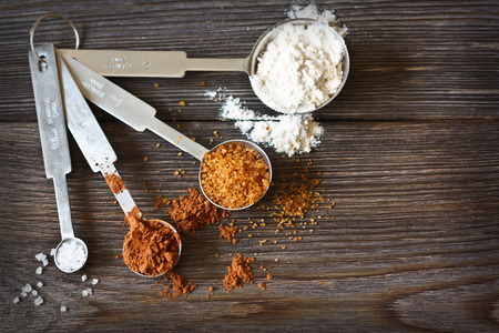 measuring spoons: Food ingredients and kitchen utensils for cooking on a wooden board. Measuring spoons with cocoa, flour and brown sugar.  Stock Photo