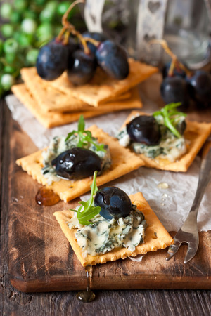 crackers: Delicious clue cheese crackers appetizer with honey and arugula on an old cooking board.