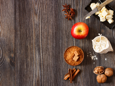 Ingredients for apple pie cooking. Fresh red apple, butter, flour, brown sugar, nuts and spices on a rustic wooden background. photo
