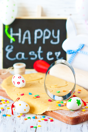 Easter cooking. Egg cookie cutter on a sweet dough and colorful chocolate eggs. photo