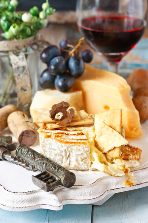 Still life with delicious cheese, red wine, fruits and nuts. photo