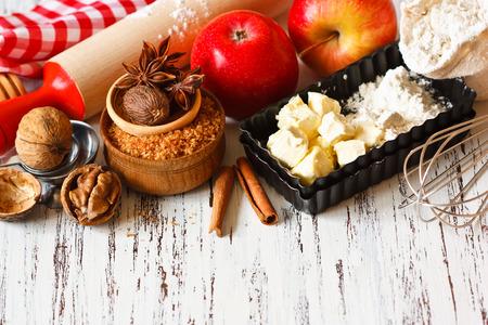 pastel de manzana: Ingredientes para cocinar el pastel de manzana. Manzana roja fresca, mantequilla, harina, azúcar moreno, frutos secos y especias sobre un fondo de madera rústica.