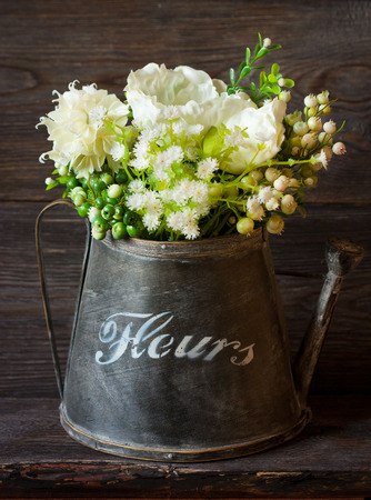 Beautiful white flowers in vintage watering can on old gargen board. photo